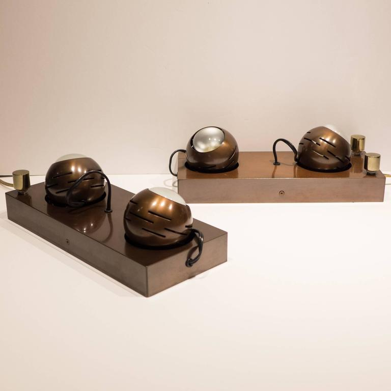 Pair of double eyeball sconces in bronzed steel, each composed of two spherical fixtures attached by magnet, with separate on/off brass dimmer switches. Designed by Angelo Lelli for Arredoluce, circa 1970s. With original Arredoluce paper labels,