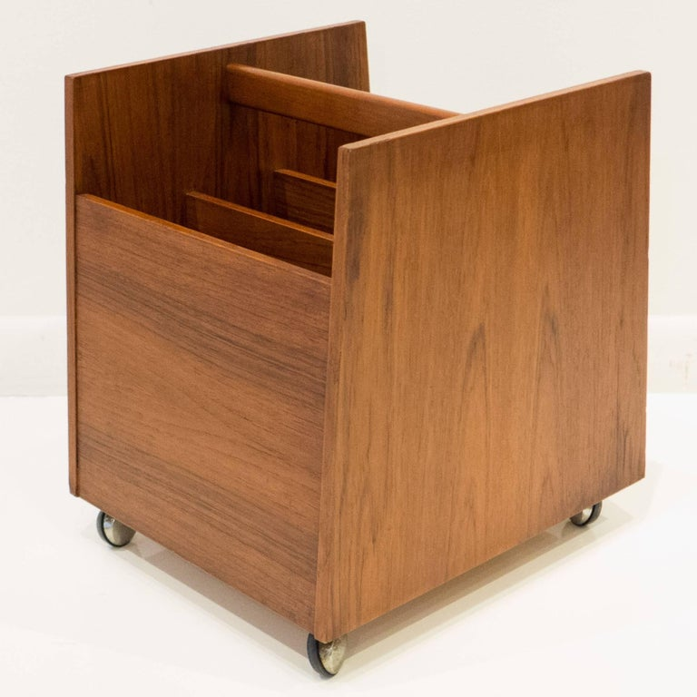Teak-veneered magazine or record bin with vertical dividers, on casters. Designed by Rolf Hesland for Bruksbo, Norway, circa 1960s. Retains original label. The dividers slide out for larger loads.