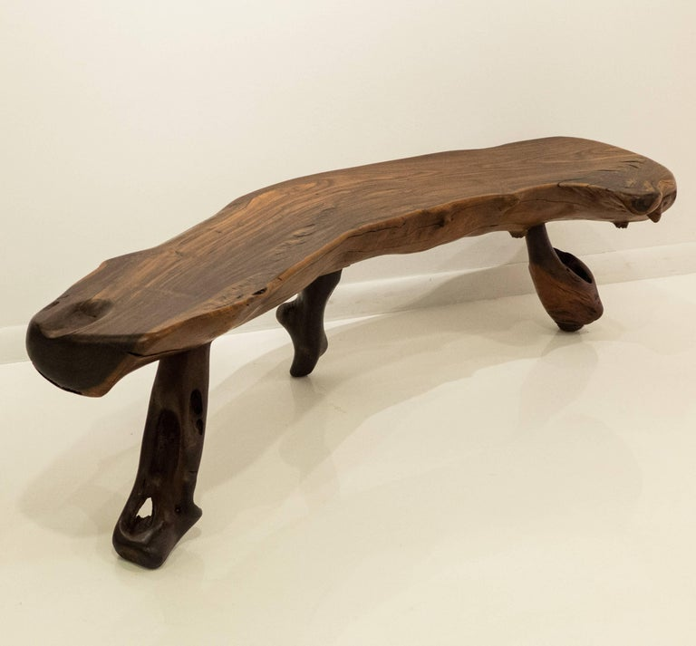 Sculptural bench or table in solid Brazilian rosewood with Brazilian rosewood burl legs. Purchased in Mexico, 1960s. A well-crafted piece featuring a spectacularly grained, polished live-edge top with three burl legs each with its own abstract
