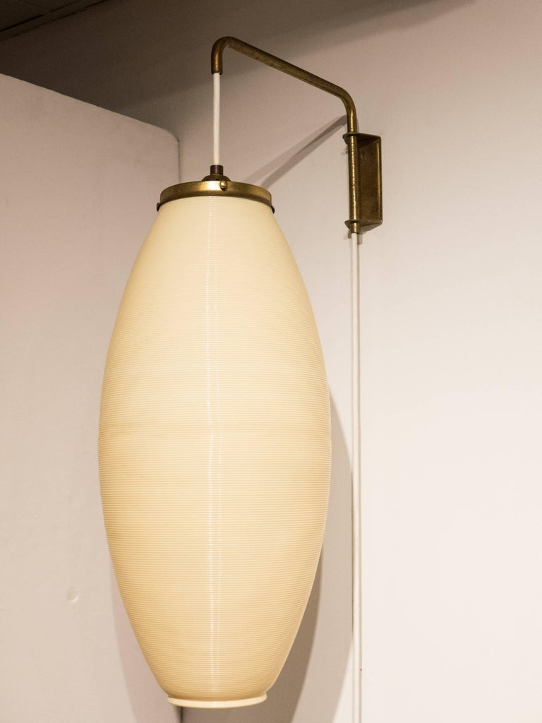 Adjustable wall-hanging lamp with cigar-shaped Rotaflex shade, brass-plated fittings, and an iron counterweight. Pivots and adjusts up and down. An early postwar (circa 1950-55)) usage of Rotaflex, a French-innovated coiled plastic used in light