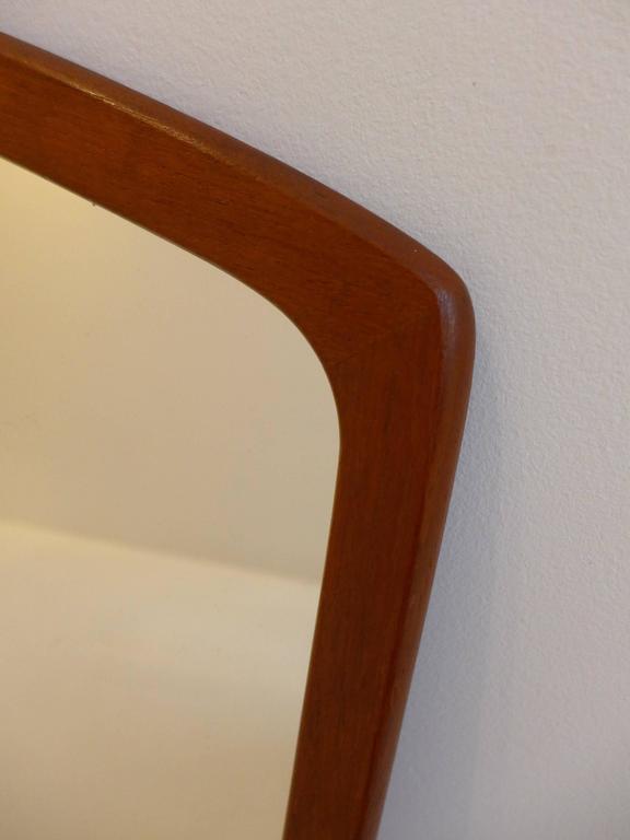 Eccentric-shaped mirror with curvilinear teak frame, made circa 1960s by Aarhus Glasimport og Glassliberi. With original paper label on back.