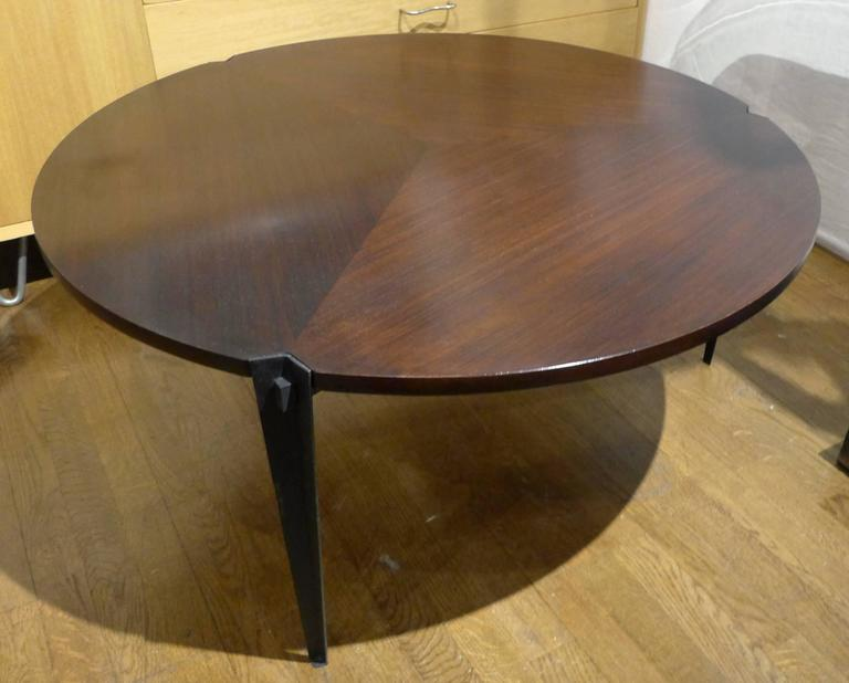 Round cocktail table with tripod enameled steel base. Top is reversible; rosewood on one side, mahogany on the other-both sides with pie-shaped patterning. Designed by Osvaldo Borsani for Tecno, circa 1960. Elegant details throughout. Top has been