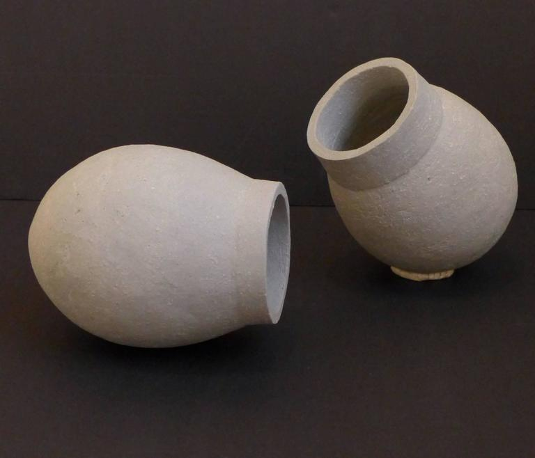 Sculptural vessels in an ovoid form with walled aperture. Hand-built of gray chamotte Limoges porcelain by Swiss ceramic artist Sonja Duo-Meyer (b. 1953) and executed circa 1995. The surface is textured and slightly variegated, imparting a