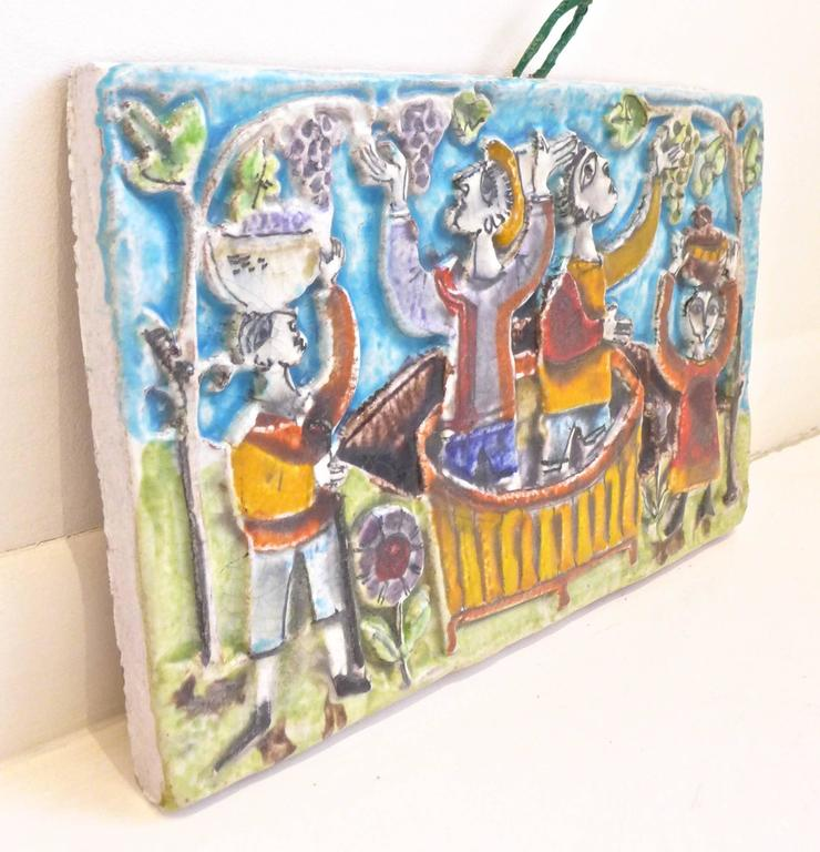 Large hand-painted Majolica relief plaque depicting wine making, by Sicilian ceramist Giovanni De Simone, executed, circa 1960s. A superb example of this maker's work, with vividly colored and highly stylized figures set in a Mediterranean