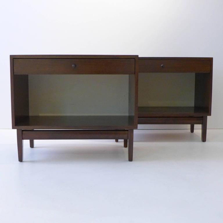 Pair of nightstands of walnut with white Micarta rear panels and painted metal pulls. Designed most likely by Kipp Stewart as part of his American Design Foundation line for Calvin Furniture, circa 1950s. With the original metal tag.