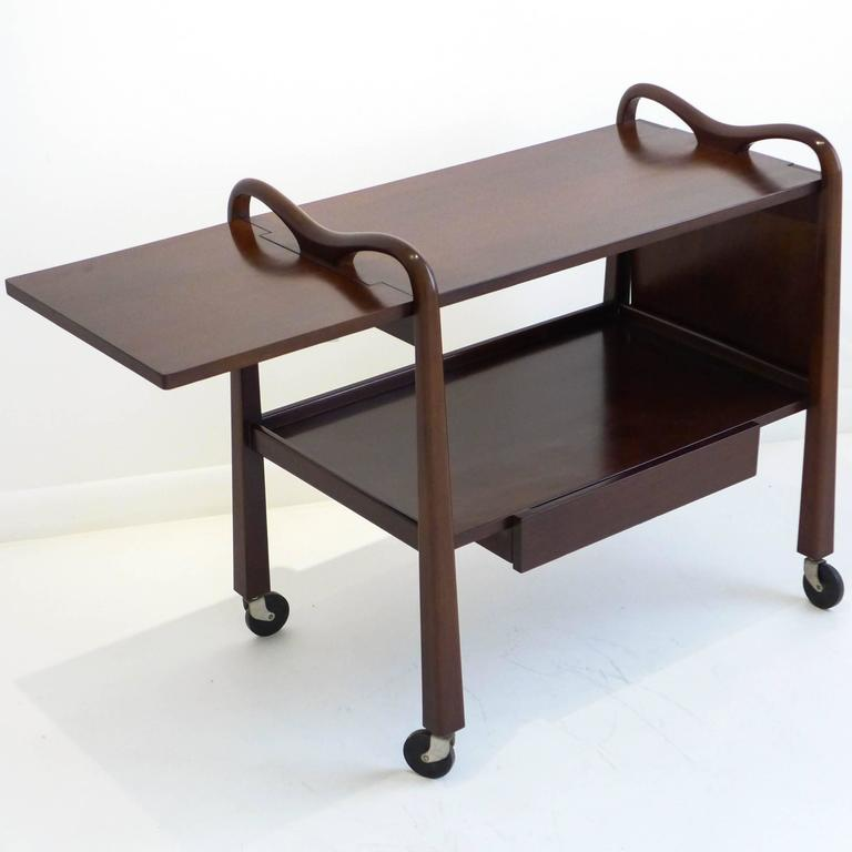 Rare rolling bar or serving cart of Cuban mahogany with integrated handles, flaring legs, a medial drawer and sides panels that can be raised or lowered. An elegant design by American designer Edmond J. Spence, produced in Mexico by Industria