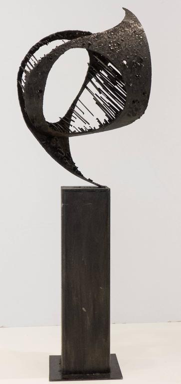 Tall Brutalist sculpture of blackened and collaged steel, perched on attached columnar steel base. Titled