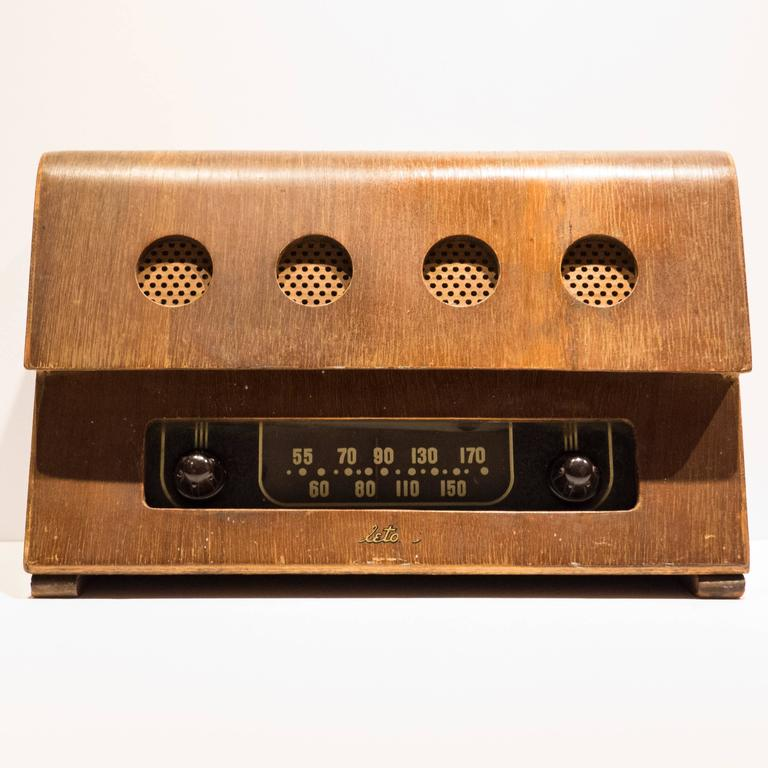 """Radio of molded and cut walnut plywood, bakelite, glass and perforated masonite. Designed by Charles and Ray Eames and produced by Evans Products for Teletone, circa 1946. As Richard Wright noted in 2004, """"this rare production radio parallels the"""