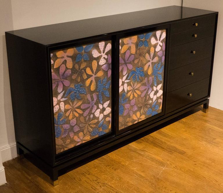 Cabinet or dresser featuring inset high-fired enamel-on-copper doors with a richly colored floral decorative motif. Dark mahogany case with brass pulls and sabots; white-lacquered interior drawer fronts and a finished, white lacquered back. Solid