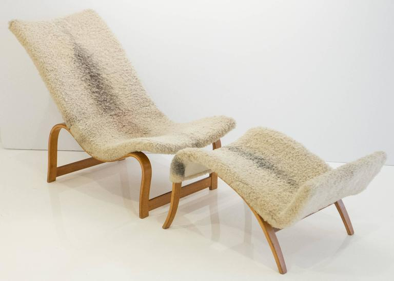 Early and rare easy chair, model 36, plus footrest, with a steam-bent beech plywood frame and original canvas webbing under vintage sheepskin upholstery. The easy chair is an early version with uniformly thick legs and stretchers near the floor.