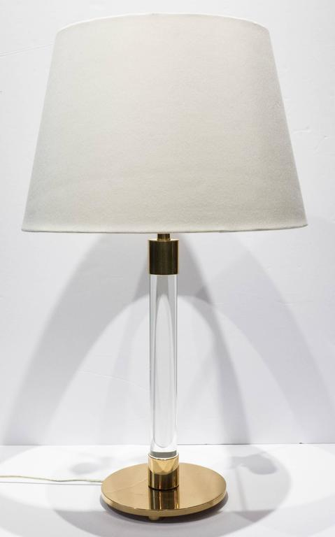 Hansen table lamp with uncommon (footed) round base, along with glass rod and well-machined brass fittings. A Minimalist and elegant design, scarcely seen in a table version. The cord is inset into a channel in the rear of the glass rod, and is