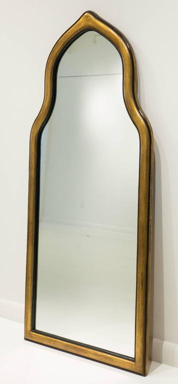 Handcrafted pier or wall mirror with a Moorish arch. Carved wooden frame with patinated gilt gesso and paint. Made by Friedman Brothers, the venerable New York City firm, circa 1950s. 52 inches tall. In excellent condition, still with the original