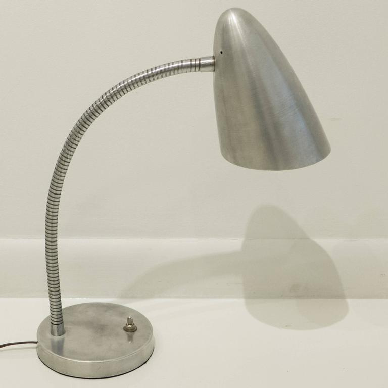 Flexible gooseneck table lamp with a spun aluminum reflector, satin chrome gooseneck, and cast aluminum base, designed by Harry Handler for General Lighting Co, produced circa 1947. An early postwar modernist lighting design that made its way into