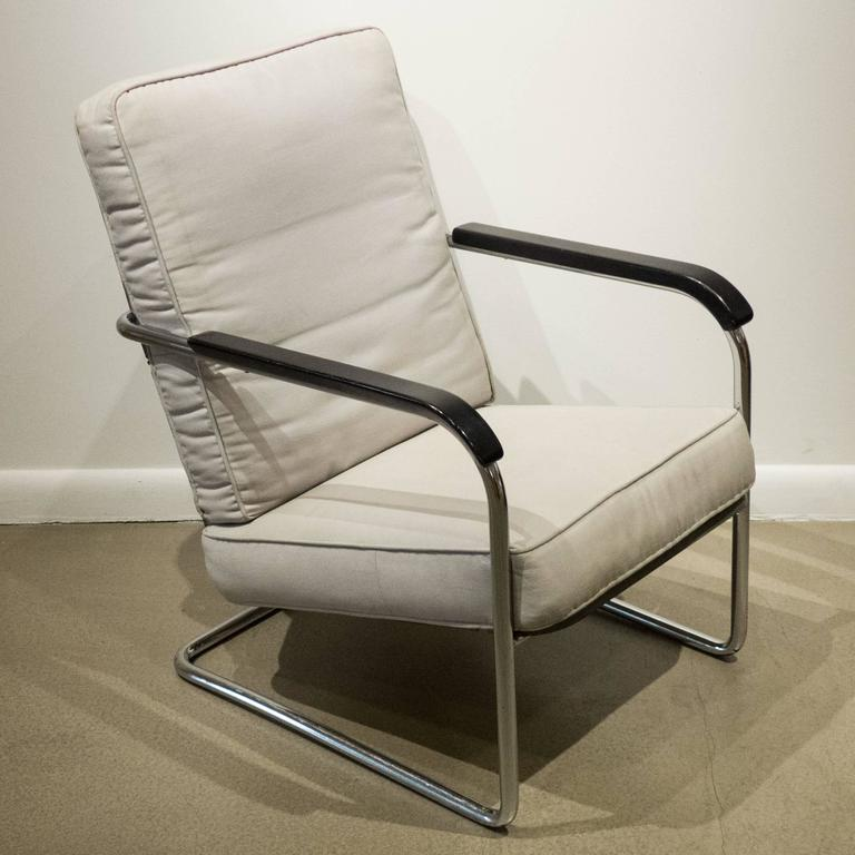 High-back armchair with a cantilevered tubular chrome frame with gray-painted flat and angled steel seat and back and steel coils and painted wooden armrests. Designed by Werner Max Moser and produced by Embru Werke/Wohnbedarf, circa 1934. The loose