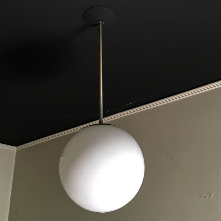 Pendant fixture with spherical milk glass globe and satin aluminum fittings. Designed and produced by Kurt Versen, circa 1937. A Bauhaus-inspired design, befitting a Swedish-born designer who studied in Germany before emigrating to the United States