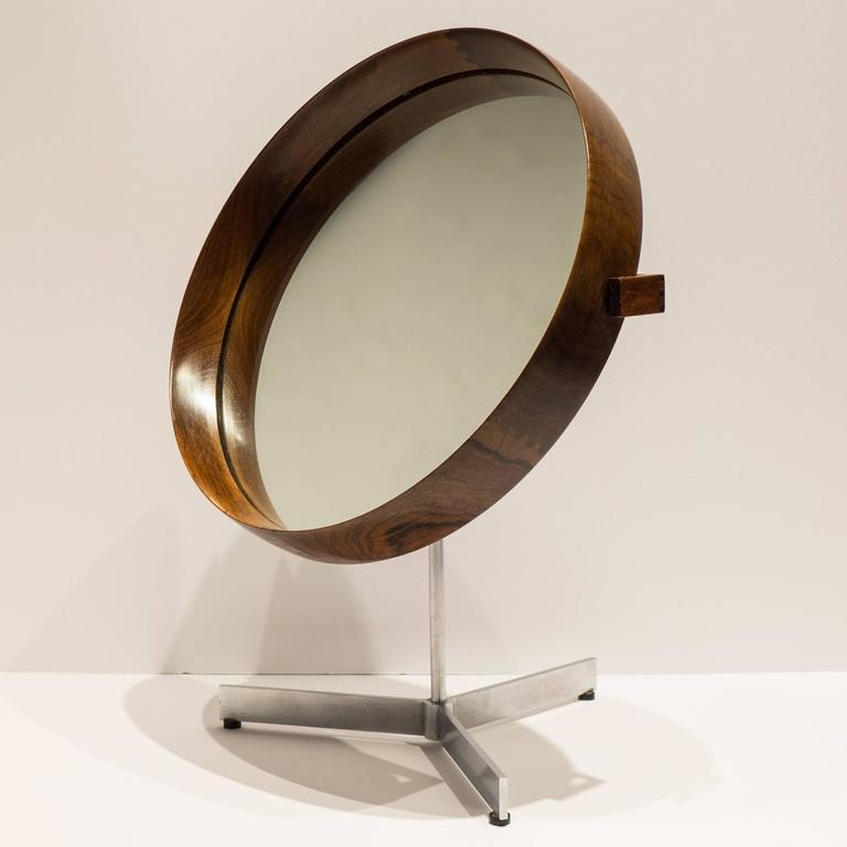 Pivoting and swiveling table mirror designed by Uno and Osten Kristiansson for Luxus Vittsjo of Sweden, circa 1960s. A luxe version of this elegant, well-made, and prized modernist object in beautifully figured rosewood with a leather-clad back and