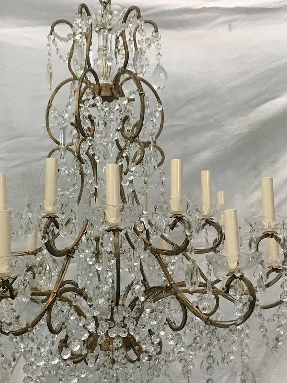 A large Italian, circa 1920s gilt metal and crystals chandelier with 18 lights. Original patina.  Measurements: Diameter 34