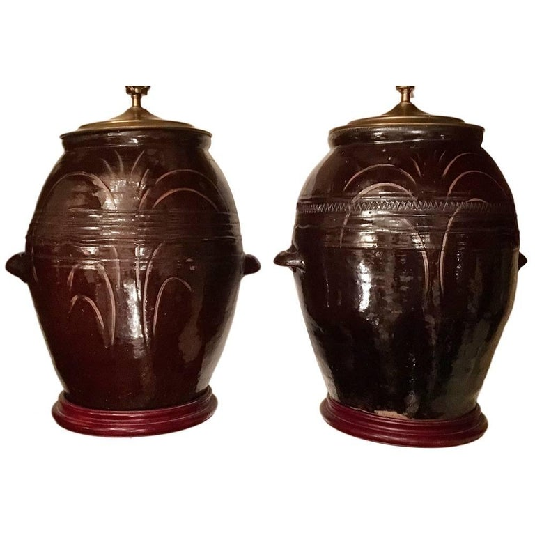 """Pair of large Italian, circa 1940s ceramic table lamps with wooden bases. Measurements: 19"""" height of body 19"""" width of body."""