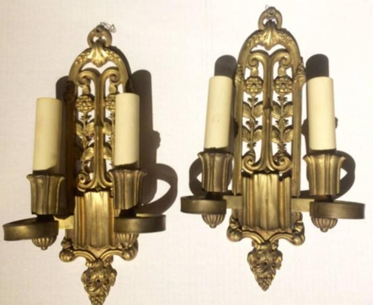 Pair of circa 1900 cast bronze sconces with two lights. Foliage motif on backplate, original patina.