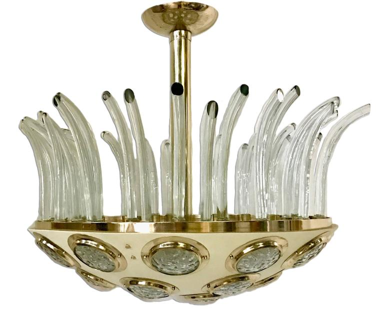 Circa 1960's Italian Moderne light fixture, gilt with painted body. Glass insets on body and glass decorative elements.  10 interior lights  Measurements: 33″ Diameter 28.5″ Present drop