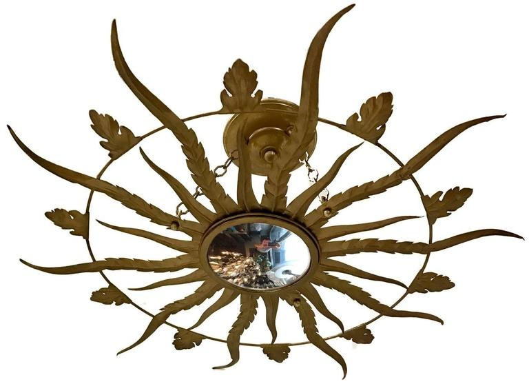 French, 1940s, gilt metal sunburst light fixture with convex mirror inset. Measurements: Diameter: 25