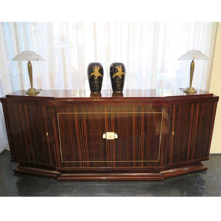 Elegant Macassar ebony sideboard with mahogany details. Original ivory hardware and thin inlayed ivory border around center doors. Signed by Majorelle on right side of piece. Slanted frame on sides with prominent middle doors. Shelving in center