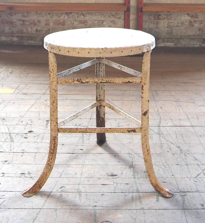 """Vintage Industrial three-legged stool - steampunk distressed painted metal medical style, for use in factory or work shop. Seat is 14"""" in diameter. Base measures: 16 34"""" 16 3/4""""."""