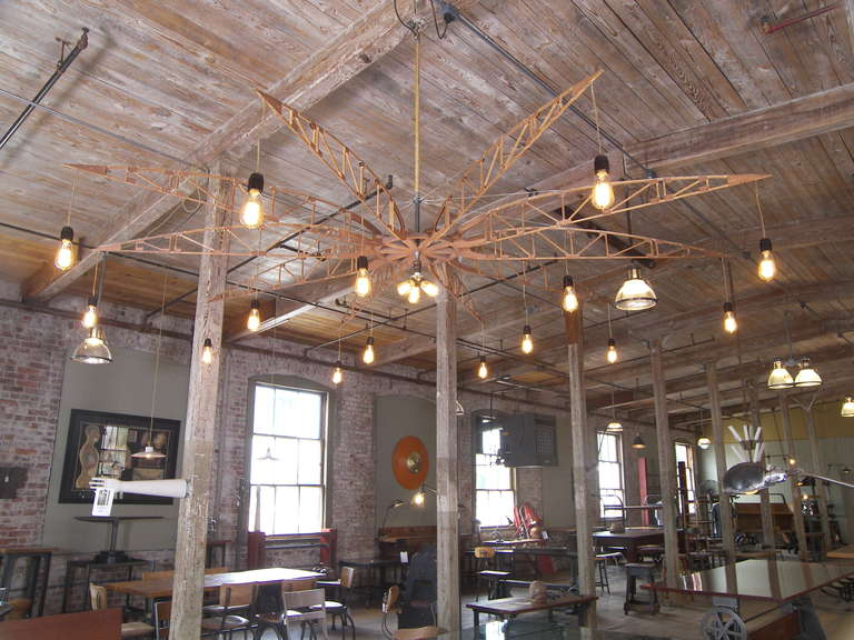 Chandelier constructed from ten wooden airplane trusses with eighteen Edison light bulbs including a three bulb cluster in the center. Diameter is 96