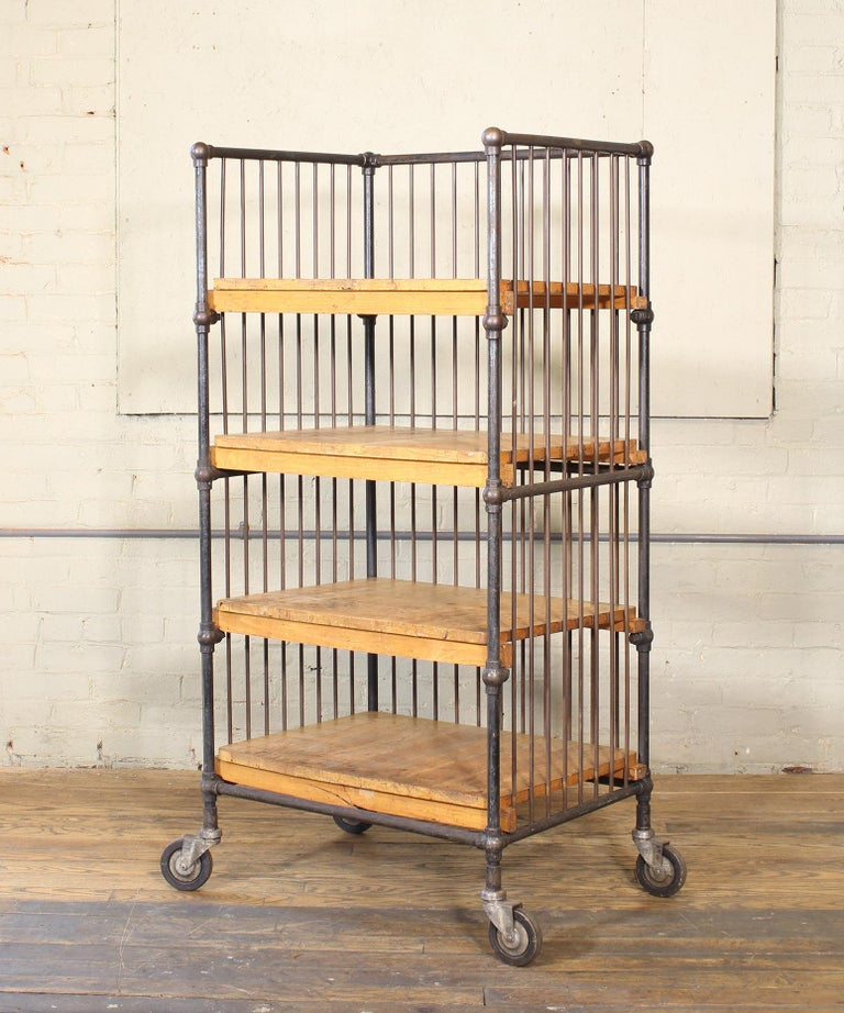 Authentic vintage four-shelf printers bindery rolling bar cart with bubble joints and swivel castors. Overall dimensions: 27 1/2