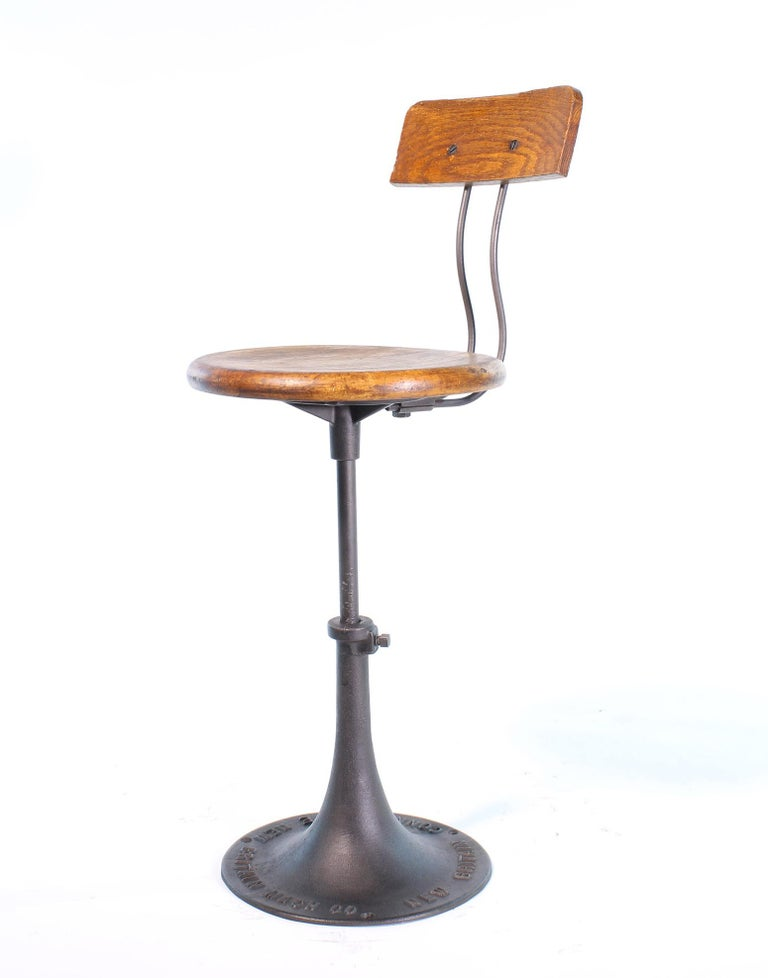 Authentic antique wood and cast iron adjustable factory stool with back made by The New Britain Machine Company of Connecticut. The seat diameter measures 14