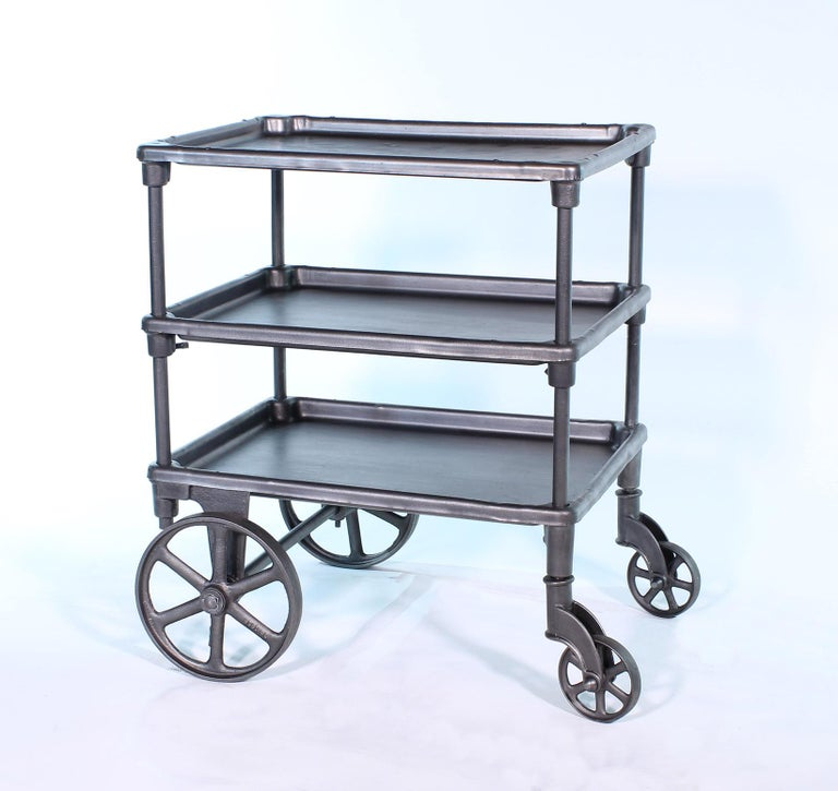 Authentic early 1900s cast iron and steel adjustable three-tier rolling bar cart on castors. Middle shelf is adjustable in height. Top measures 26 1/4