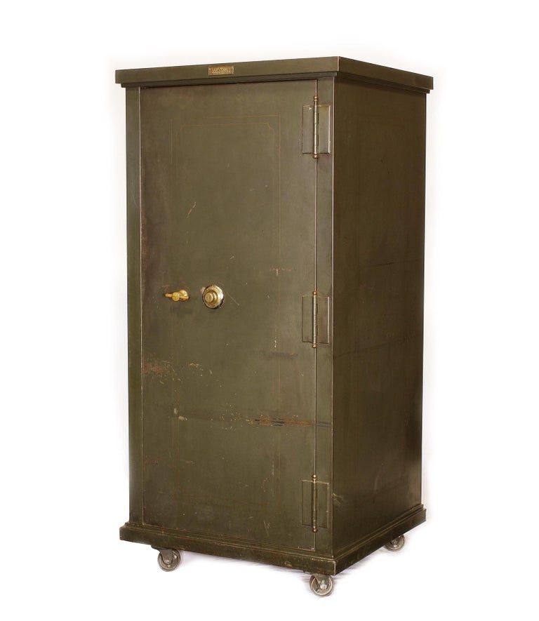 Vintage steel bank / gun safe made by The Safe-Cabinet Co. Features two drawers, adjustable shelves, one storage compartment, four swivel castors and brass hardware. Three labels on safe.