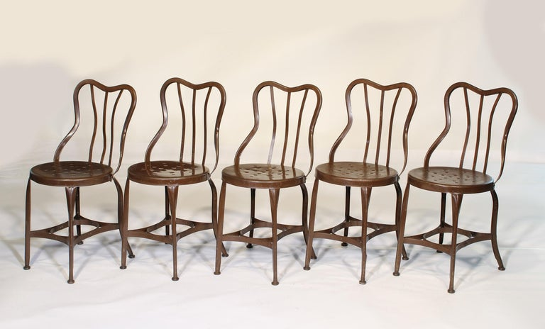 Authentic set of five 1920s steel cafe / ice cream chairs by Toledo. Distressed brown paint with gliders and sloped perforated seats. All chairs have been cleaned and checked for stability. Measurements: 31 7/8