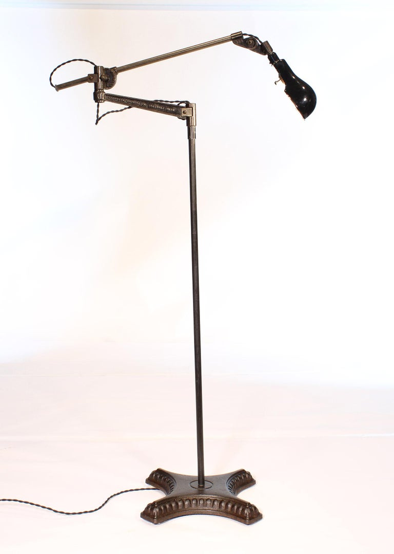 Authentic vintage industrial adjustable Woodward cast iron and steel floor lamp / reading light. Lamp is fully adjustable, with a swivel top, and can be formed into a variety of positions. Overall height is adjustable from 55 1/2