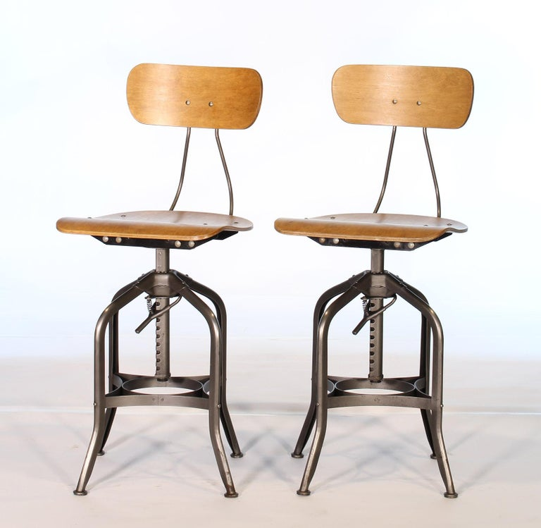 Pair of authentic vintage industrial bent plywood adjustable stools made by Toledo. Stools have been completely taken apart, cleaned, reassembled and checked throughout. A great choice for bar stools or kitchen counter seating. Seat height is