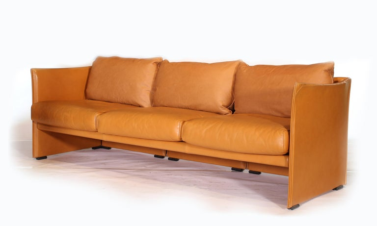 Authentic vintage Mid-Century Modern three-seat tilbury sofa by Mario Bellini in light brown leather. Three back cushions have been replaced to a close match. Measures: 84