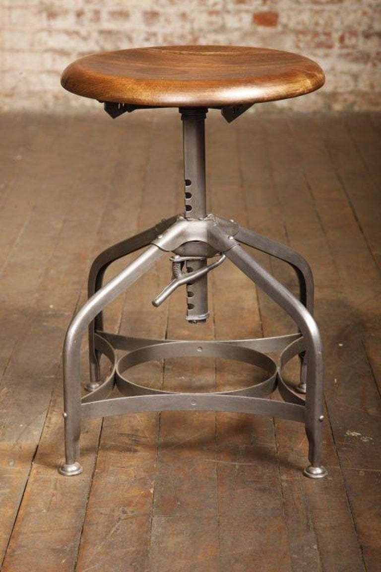 Vintage industrial backless adjustable authentic Toledo stool. Scooped solid wooden maple seat adjusts from 16 1/2 - 24
