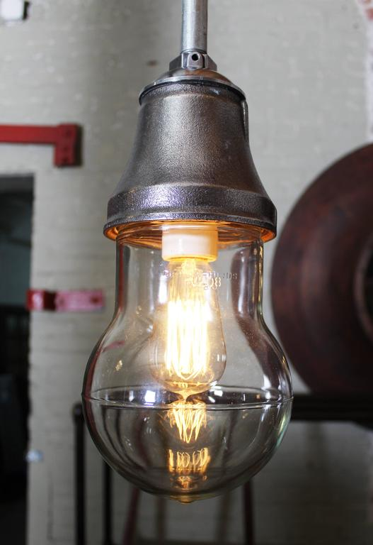"""Bulbus"" Industrial vintage hanging, ceiling cast iron, steel and glass pendant light lamp shown with two types of Edison Bulbs. Steel pole included and cut to your specifications. Glass Measures 6"" x 8"", and the Light is 13"" tall."