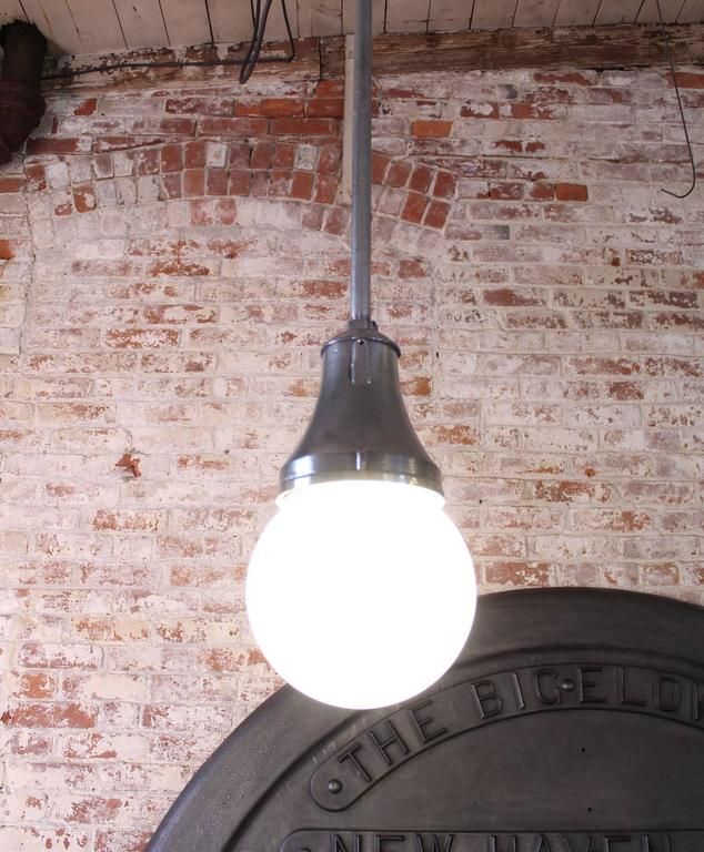 Cast iron, steel and frosted white glass globe industrial hanging, ceiling pendant lamp, light. The glass measures 8