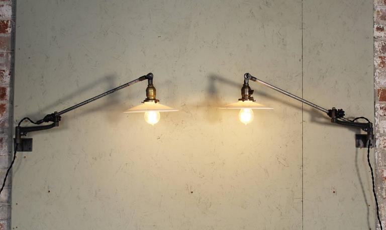 Pair of vintage Industrial milk glass O.C. White wall task lamps, lights with Edison Bulbs. Articulating lamps with cast iron knob adjustment fittings. Milk glass shades measure 8 1/4