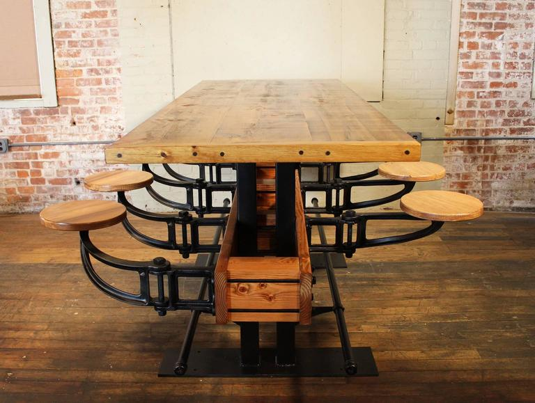 Swing out seat restaurant bar / pub height table. Made from wood, cast iron and steel. Featuring eight cast iron and wood swing out seats, foot rails and 2