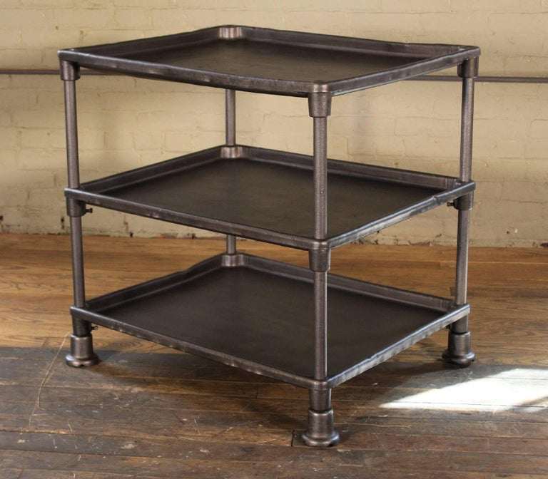 Authentic vintage-Industrial three-tier adjustable factory table. Features cast-iron feet and steel shelves, the bottom two are height-adjustable.