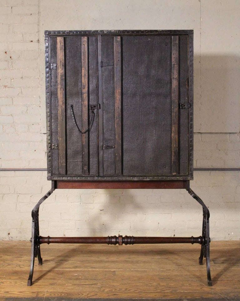 Vintage Industrial cast iron and wood secretary storage cabinet. In two pieces, top is not attached. Cast iron base with wooden spindle, and San Francisco newspaper, circa 1940s covering the inside drawers. Multiple cubby holes for storage. Overall