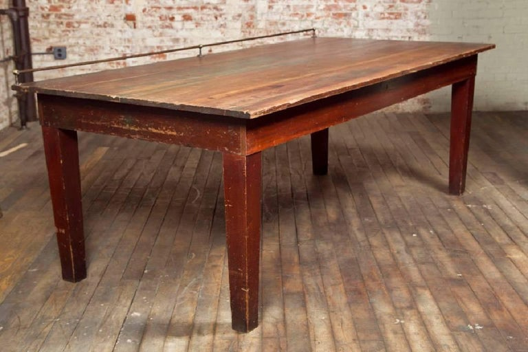 """Vintage industrial wood retail display table with brass backstop. 96"""" x 47 1/2"""" x 34 1/2"""" in height (37"""" in height including rail)"""
