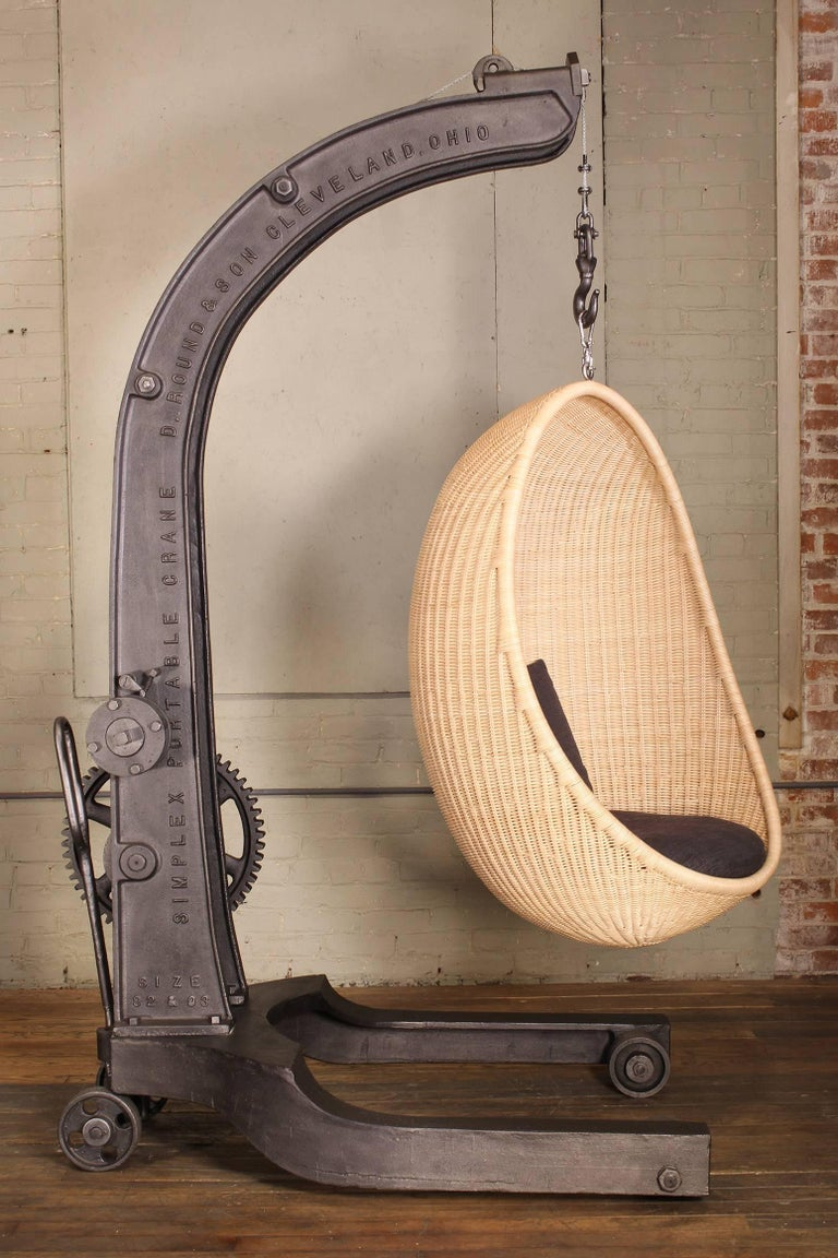 1920s cast iron manual crank engine hoist with woven rattan Nanna Ditzel hanging interior egg chair in natural, with charcoal cushion. Seat height is adjustable by engaging the crank mechanism handle. Dimensions of the chair are width 85 cm (33.5