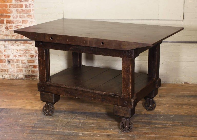 Vintage Industrial rolling kitchen island / table. Made of cast iron, steel and wood, features four swivel cast iron castors. Cast iron top measures 58 3/4