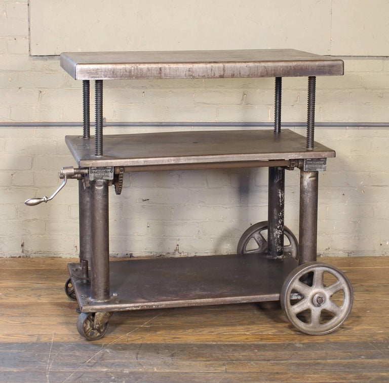 Original vintage Industrial adjustable metal, steel rolling three tier lift bar cart or table with cast iron casters / wheels. Measure: Top is adjustable in height from 25 1/4