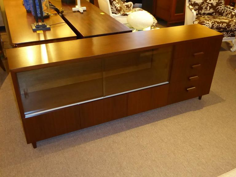1950s walnut credenza with drawers, glass doors and bottom cabinet. Exhibiting a wonderful scale of long and narrow, not too deep, this credenza was a custom bespoke design by Robert Law Reed, noted Miami architect of the early to Mid-Century.
