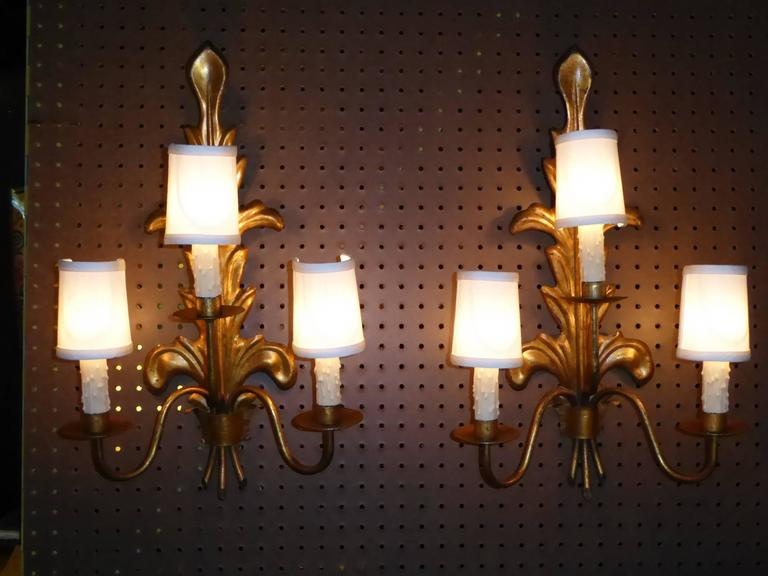 Fine Mid-Century appliques from Barcelona. Acanthus leaf in gilt tole backs with three curling branches ending in bobeches and wax drip candles. Rewired and with new UL candelabra sockets. 40 watts max each. Crossbar in back for hanging. Price is