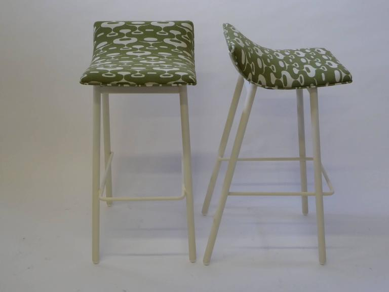 Originals from the 1950s, this pair of bar stools are early ergonomic designs and a comfy perch at the bar. These stools are sturdy and comfortable with a gentle low-rise back support and footrest. Re-lacquered in a soft white satin and with